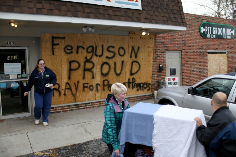 "Melisa Hutchings (L), Tracy Reust and Daniel Wentz walk past a sign reading, ""Ferguson Proud Pray for Peace and Progress,"" as they carry a cat from the Ferguson Animal Hospital where they placed plywood on the windows to try to protect the business from any violent reaction to the grand jury decision on November 17, 2014 in Ferguson, Missouri. The area around St Louis, Missouri prepares for the release of the grand jury decision in the shooting death of Michael Brown by Darren Wilson, a Ferguson police officer. (Photo by Joe Raedle/Getty Images)"
