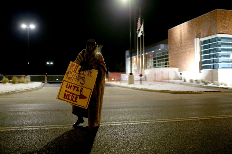 A demonstrator stands next to the Ferguson police station while protesting the shooting death of Michael Brown by a Ferguson police officer on November 17, 2014 in St. Louis, Missouri. The area around St Louis, Missouri prepares for the grand jury decision in the shooting death of Michael Brown by Darren Wilson, a Ferguson police officer. (Photo by Joe Raedle/Getty Images)
