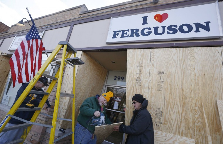 "Workers board up the ""I Love Ferguson"" store in preparation for the grand jury verdict in the shooting death of Michael Brown in Ferguson, Missouri, November 18, 2014. The grand jury is expected to reach a decision this month on whether to indict Darren Wilson, the white police officer who shot and killed the 18-year-old Brown, who was black, on Aug. 9 in the St. Louis suburb of Ferguson. (Jim Young/Reuters)"