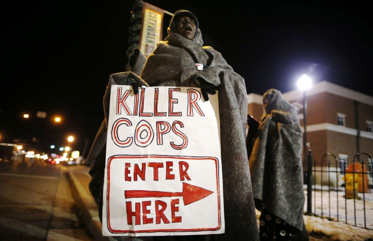 A demonstrator yells during a protest over the shooting death of Michael Brown in front of the Ferguson Police Department in Ferguson, Missouri, November 17, 2014. Missouri's governor declared a state of emergency on Monday and authorized the state's National Guard to support police in case of violence after a grand jury decides whether to indict Darren Wilson, a white police officer who fatally shot Brown, unarmed black teenager. (Jim Young/Reuters)