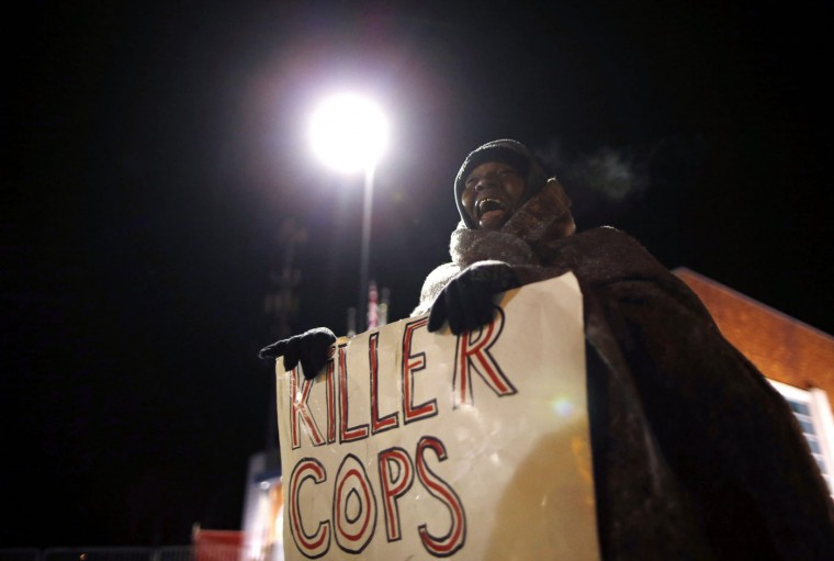 A demonstrator yells during a protest over the shooting death of Michael Brown in front of the Ferguson Police Department in Ferguson, Missouri, November 17, 2014. Missouri's governor declared a state of emergency on Monday and authorized the state's National Guard to support police in case of violence after a grand jury decides whether to indict a white police officer, Darren Wilson, who fatally shot an unarmed black teenager. (Jim Young/Reuters)