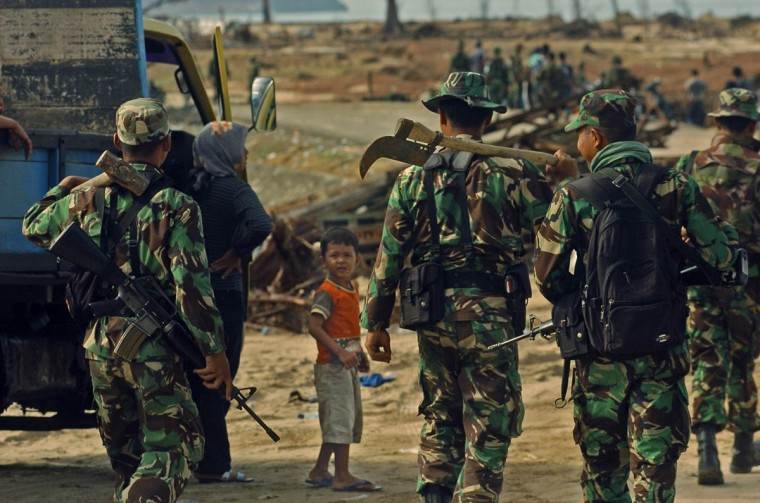 A child watches 3 Indonesian Military Police walk with weapons of combat and of rebuilding Wednesday, Jan. 19, 2005 following a tsunami that swept through the town in December. (Karl Merton Ferron, Baltimore Sun)