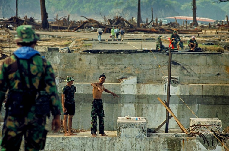 Indonesian Military Police focus their attention on a bridge over the Lhok Nga River for repair Tuesday, Jan. 18, 2005 following a tsunami that swept through the town in December. (Karl Merton Ferron, Baltimore Sun)