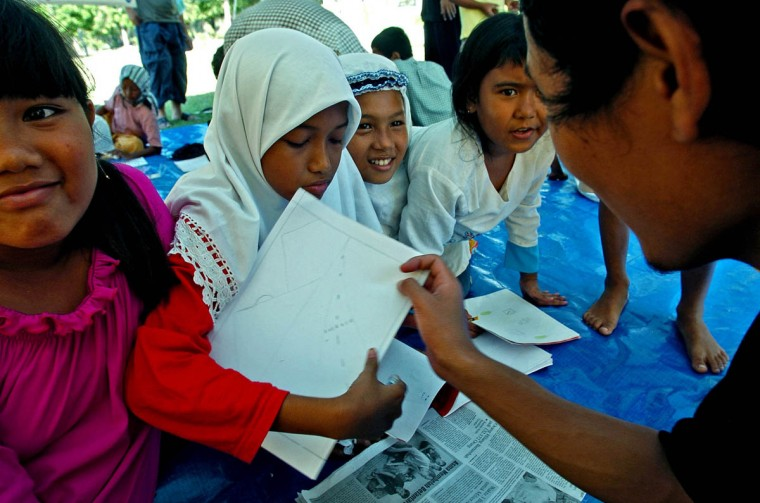 Humaira Puspitadewi, 11 (second from right) squeezes in with new friends Fitria Siranggiana, 9 (left), Lia Azrina, 11 and Nurul Husna, 9, to show their teacher their progress while pausing on their project to create a drawing at Darussalem as they attempt to get back on their feet January 14, 2004 after a tsunami destroyed their home and disrupted their lives in December. (Karl Merton Ferron, Baltimore Sun)