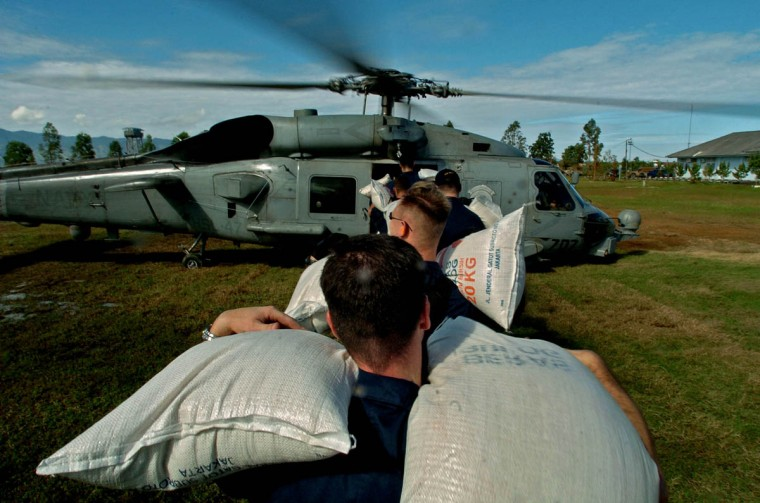 Toting sacks of rice, United States military personnel stand in line at Banda Aceh's airport to load a helicopter that will carry the items to remote areas affected by the tsunami Tuesday, Jan. 18, 2005 following a tsunami that swept through the town in December. (Karl Merton Ferron, Baltimore Sun)