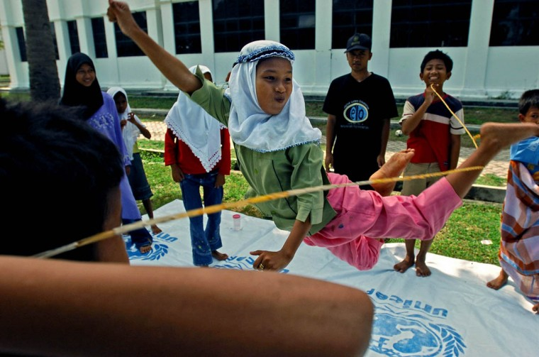 """Humaira, 11, to the delight of the other children, leaps while kicking her left foot out to catch the rubber band rope held by classmates in a game opposite of the """"limbo."""" (Karl Merton Ferron, Baltimore Sun)"""