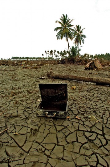 With the stench of rotting flesh nearby, a briefcase rests 2 kilometers away from the shoreline (the coconut trees at horizon in background mark the beach area) swept inland by the Christmas tsunami at village Rukoh. (Karl Merton Ferron, Baltimore Sun)