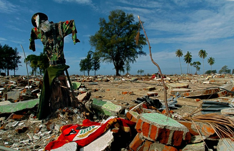 An Indonesian Military uniform with flowers placed at the area where the head would be stands like a scarecrow, erected at the site where the building of Batallion Infantry 112 once stood as a monument Wednesday, Jan. 19, 2005 following a tsunami that swept through the town in December. One website quotes an Aceh official that 500 or more military personnel are missing. (Karl Merton Ferron, Baltimore Sun)