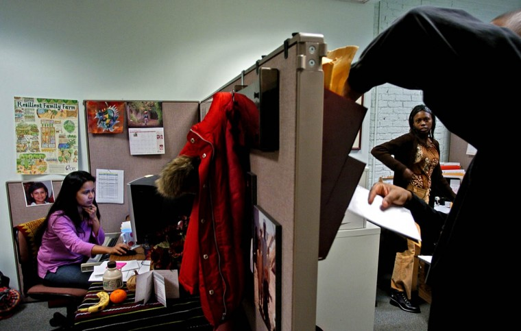 Chadreyee Banerjee of Catholic Relief Services works in her work space while mail clerk Chris Stanley drops mail for Tammie Jones, Administrator for the Eurasia region at CRS Wednesday, Jan. 5, 2005. (Karl Merton Ferron, Baltimore Sun)