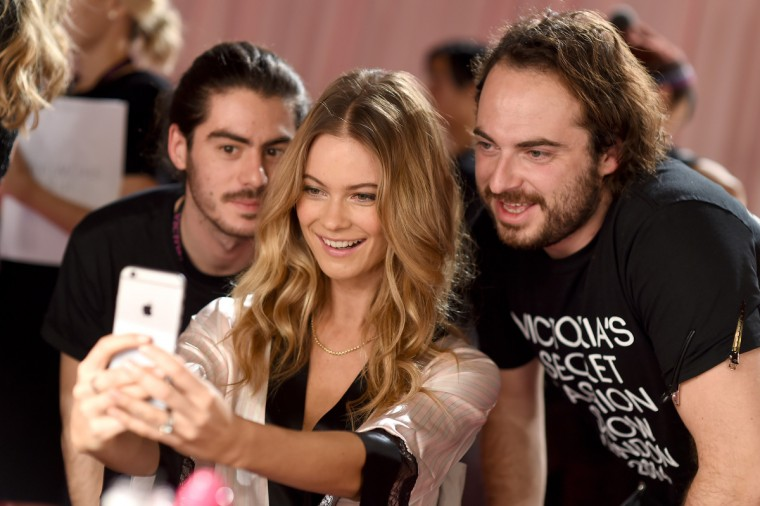Victoria's Secret model Behati Prinsloo poses with stylists seen backstage prior the 2014 Victoria's Secret Fashion Show on December 2, 2014 in London, England.  (Dimitrios Kambouris/Getty Images for Victoria's Secret)