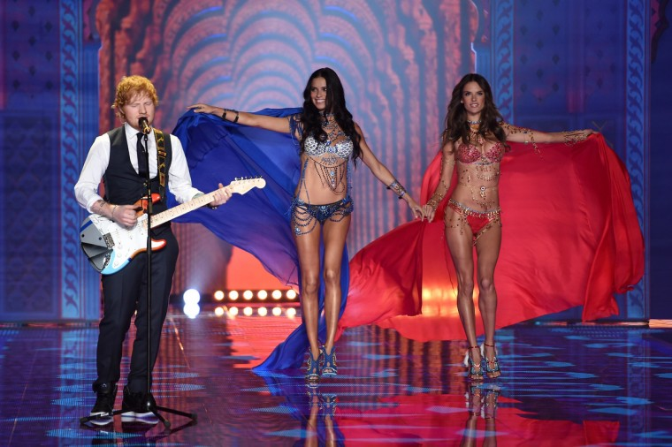 Singer Ed Sheeran (L) performs on stage as models Adriana Lima (C) and Alessandra Ambrosio walk the runway during the 2014 Victoria's Secret Fashion Show at Earl's Court Exhibition Centre on December 2, 2014 in London, England.  (Dimitrios Kambouris/Getty Images)