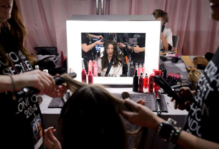 Belgian model Yumi Lambert gets her hair done backstage ahead of the 2014 Victoria's Secret Fashion Show at Earl's Court Exhibition Centre in London on December 2, 2014. (Leon Neal/Getty Images)