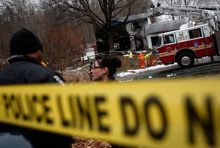 Utility workers and emergency personnel work near the site where a small plane crashed into a residential neighborhood December 8, 2014 in Gaithersburg, Maryland. The three occupants of the plane were killed in the crash, and investigators are searching for three people who are unaccounted for on the ground. (Win McNamee/Getty Images)