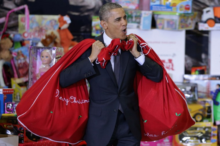 U.S. President Barack Obama, with bags slung over his shoulders, delivers toys and gifts donated by Executive Office of the President staff to the Marine Corps Reserve Toys for Tots Program at Joint Base Anacostia-Bolling in Washington, DC. For 67 years the Toys for Tots program has worked with local communities to collect and distribute toys and gifts for less fortunate children throughout the United States. (Chip Somodevilla/Getty Images)