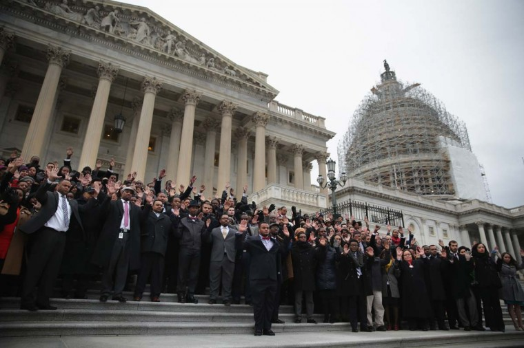 Black congressional staffers hold their hands up as they pose for a group photo during a walkout December 11, on the steps of the U.S. Capitol in Washington, DC. The staffers staged a walkout to protest over the recent Mike Brown and Eric Garner grand jury decisions. Photo by Alex Wong/Getty Images
