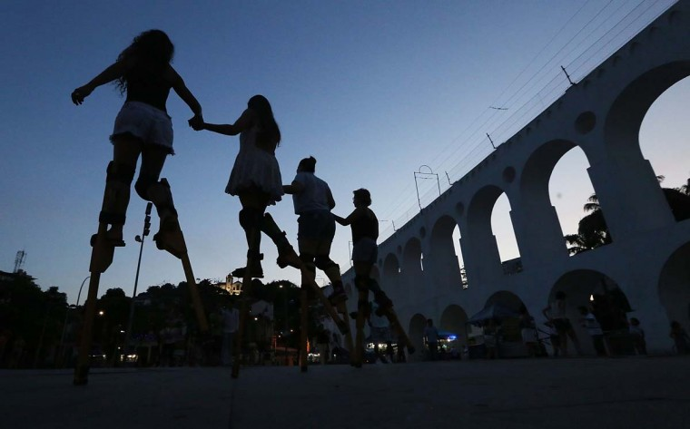 People practice walking on stilts during a stilt walking workshop as part of pre-Carnival festivities between the famed Lapa arches on December 18 in Rio de Janeiro, Brazil. Carnival begins February 13 yet practices and festivities are already underway.  (Photo by Mario Tama/Getty Images)