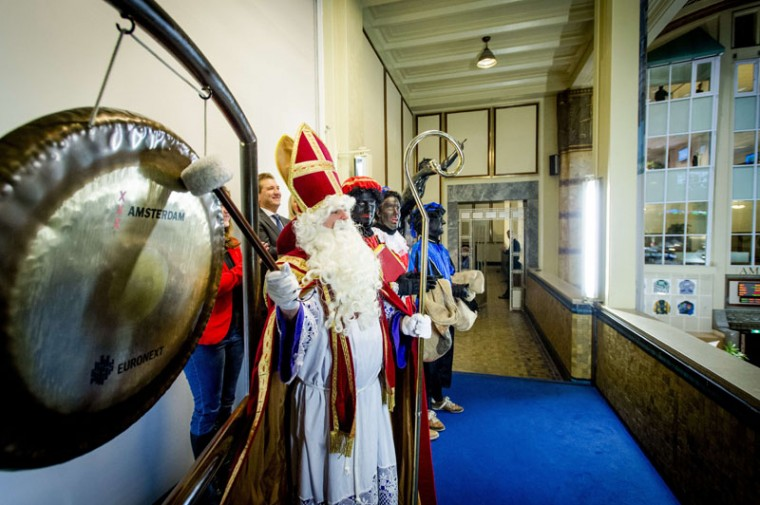 A man dressed as Sinterklaas aka Saint Nicholas (R) visits the Amsterdam Stock Exchange to beat the gong, in Amsterdam, The Netherlands, on December 5, 2014. (Robin Van Lonkhuijsen/AFP/Getty Images)