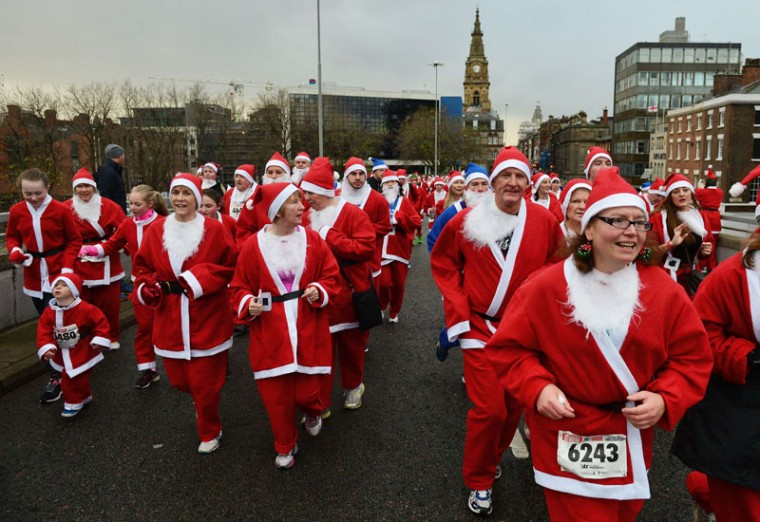 Runners dressed in Father Christmas costumes take part in the annual five kilometer Santa Dash in Liverpool, north-west England, on December 7, 2014. Organizers were hoping to attract more than10,000 runners for the 10th annual race. Many runners wear a blue suit, usually supporters of Everton football club, who refuse to run in red and white, the colors of their city rivals Liverpool FC. (Paul Ellis/AFP/Getty Images)