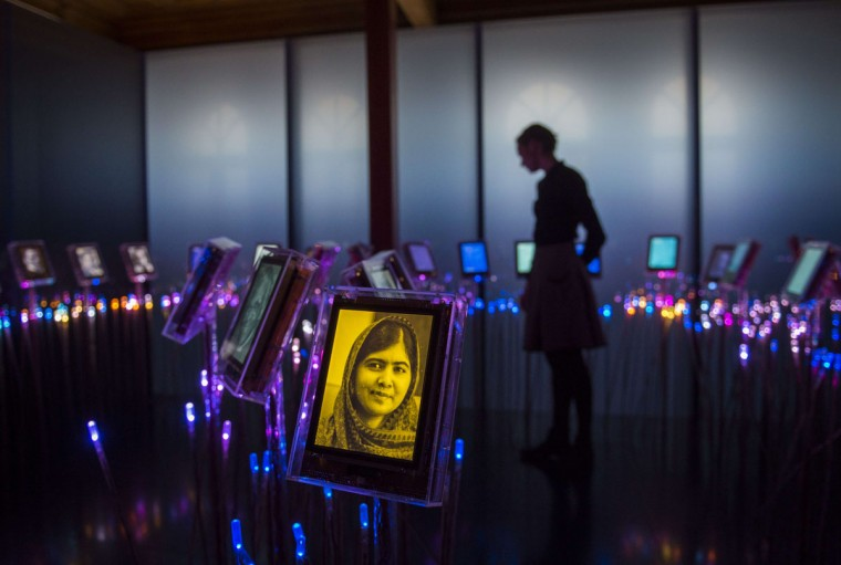 "A picture of Nobel Peace Prize laureate Malala Yousafzai is seen among portraits of previous winners in the ""peace garden"" at the exhibition at the Nobel Peace Center in Oslo on December 9, 2014. At 17-years old, the Pakistani known everywhere as Malala is the youngest ever recipient of the prize she is sharing with the Indian campaigner Kailash Satyarthi, 60, who has fought for 35 years to free thousands of children from virtual slave labour. Their pairing has the extra symbolism of linking neighboring countries that have been in conflict for decades. (Odd Andersen/AFP/Getty Images)"
