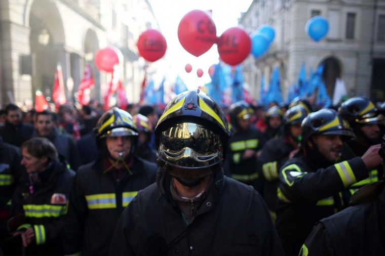 Firefighters march in downtown Turin on December 12, during an eight-hour strike called by the CGIL and UIL unions to protest against measures contained in the 2015 budget bill and against Italian Prime minister Matteo Renzi's government controversial Jobs Act, which they say threatens employment and workers' rights.  || CREDIT: MARCO BERTORELLO - AFP/GETTY IMAGES