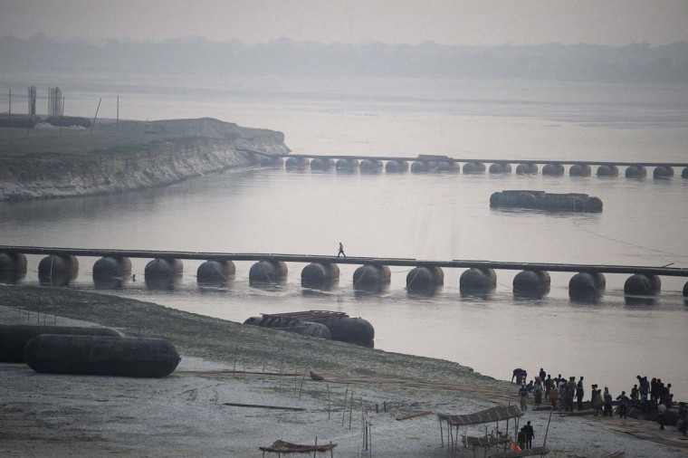 An Indian labourer crosses a newly constructed temporary pantoon bridge, installed for the Magh Mela festival, on the River Ganges in Allahabad on December 12. Magh Mela is an important annual Hindu ritual held on the banks of the Sangam in Allahabad.  || CREDIT: SANJAY KANOJIA - AFP/GETTY IMAGES