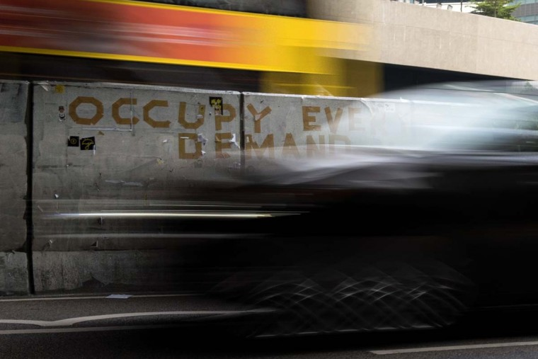 This long exposure photograph shows traffic driving past a message from the pro-democracy Occupy movement in the Admiralty district of Hong Kong on December 12. Rush-hour traffic streamed through the heart of Hong Kong for the first time in more than two months on December 12 after police cleared the city's main pro-democracy protest camp with mass arrests -- but activists vowed that their struggle would go on.    || CREDIT: ALEX OGLE - AFP/GETTY IMAGES