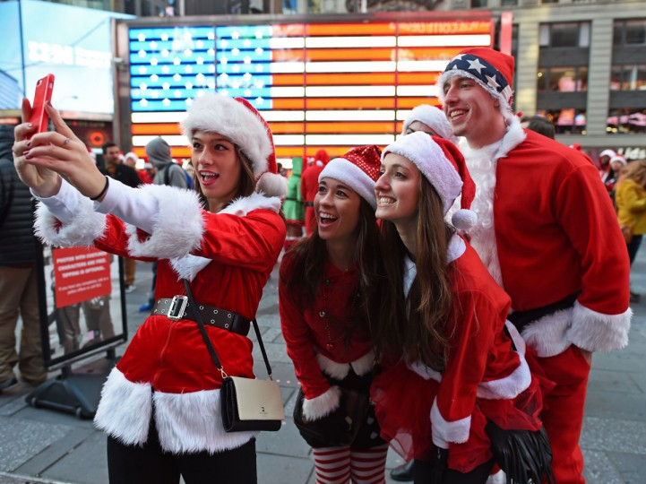 Santas and Helpers take selfies in Times Square as hundreds of Santas gather for the annual Santacon festivities on December 13, 2014 in New York. (Don Emmert/AFP/Getty Images)