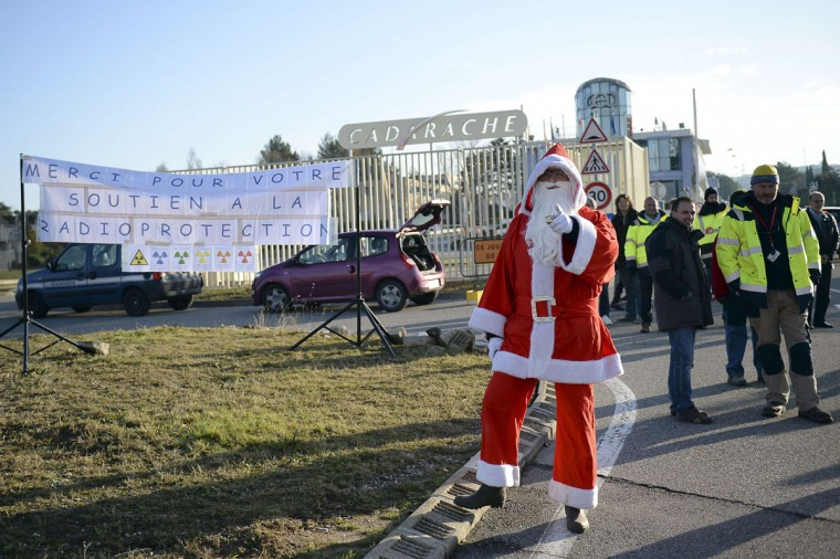A man wearing a Santa Claus costume gestures as employees of the SPR, a protection service against radiation at the CEA (French Atomic Energy Commission) nuclear site in Cadarache, southern France, block the access to the plant, during a demonstration on December 15, 2014 to protest against a reorganization plan. (Boris Horvat/AFP/Getty Images)