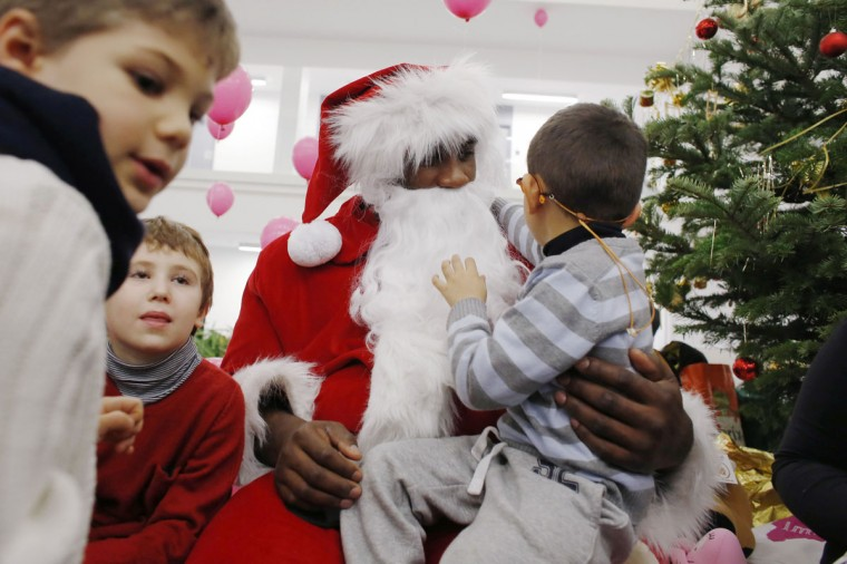 "French judo world champion and godfather of the foundation ""Imagine"" Teddy Riner dressed like Santa Claus meets with children in Paris on December 17, 2014. The ""Imagine"" foundation supports children with genetic diseases. (Thomas Samson/AFP/Getty Images)"