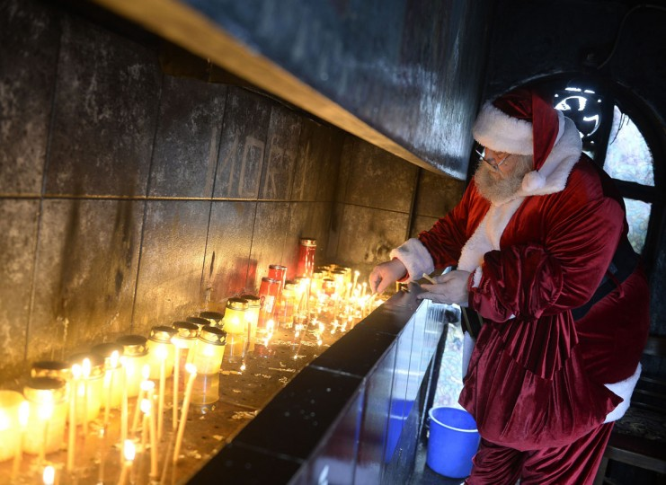A man dressed as Santa Claus lights candles at a church in Bucharest, Romania on December 18, 2014. (Alex Nicodim/AFP/Getty Images)