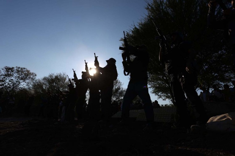 Members of a self-protection militia fire their weapons into the air during the funeral of Manuel Mora in the La Ruana Community, Michoacan State, December 18. The son of militia leader Hipólito Mora, Manuel Mora and 11 other were killed on December 16th during clashes with other groups of  rural police.     CREDIT: STRINGER -AFP/GETTY IMAGES