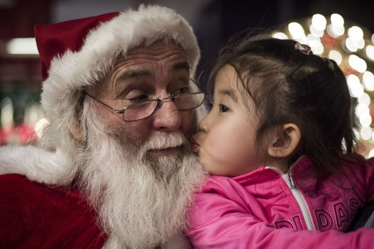 A girl kisses a Santa Claus at the Intercontinental hotel of Beijing, on December,19, 2014. (Fred Dufour/AFP/Getty Images)
