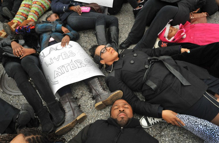 On Reisterstown Road, near the entrance to the shopping center, the protesters formed a circle and many laid down to stage a die-in. (Amy Davis / Baltimore Sun)