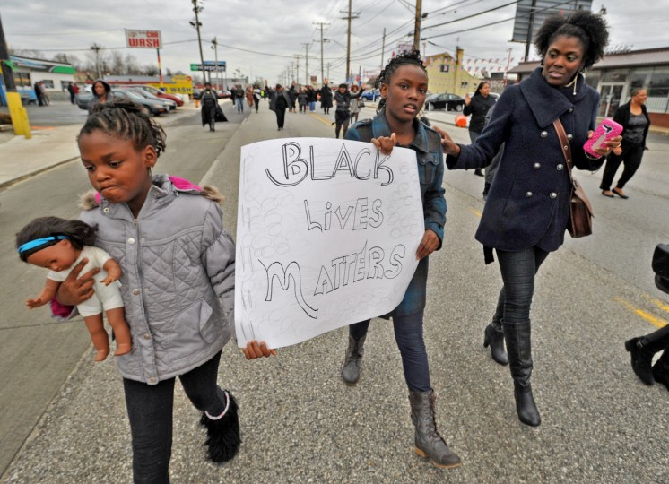 Sisters Jaire, left, and Jaelyn Long, center, march with their mother, Matisia Jones, right. More than 500 protesters marched from Empowerment Temple Church on Primrose Avenue north on Reisterstown Road to Reisterstown Road Plaza. (Amy Davis / Baltimore Sun)