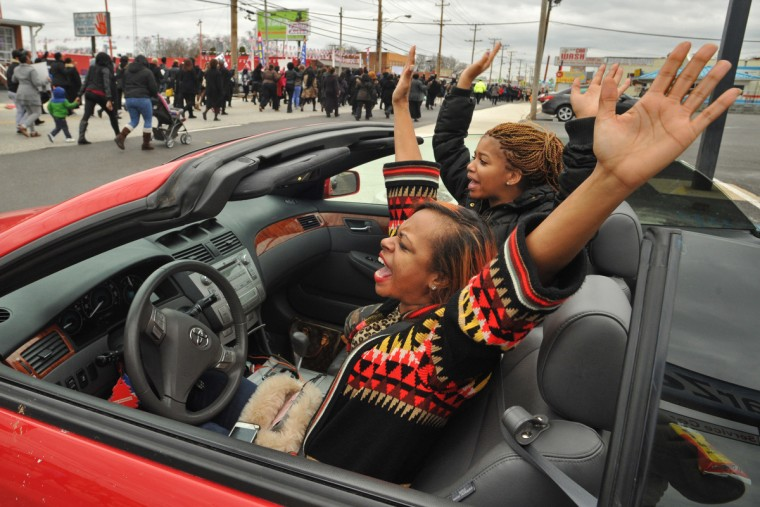 Driver Krystal Smith and friend Erica Cunningham, blocked from entering Reisterstown Road due to the march, raise their arms and chant in support of the marchers. (Amy Davis / Baltimore Sun)