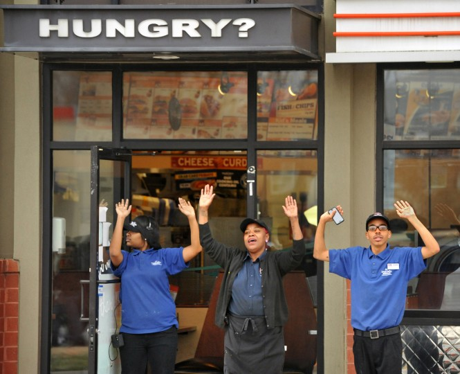 "Workers at an A&W fast food restaurant on Reisterstown Road raise their arms in support of the marchers. More than 500 protesters marched from Empowerment Temple Church on Primrose Avenue north on Reisterstown Road to Reisterstown Road Plaza for ""Black Lives Matter Sunday."" (Amy Davis / Baltimore Sun)"