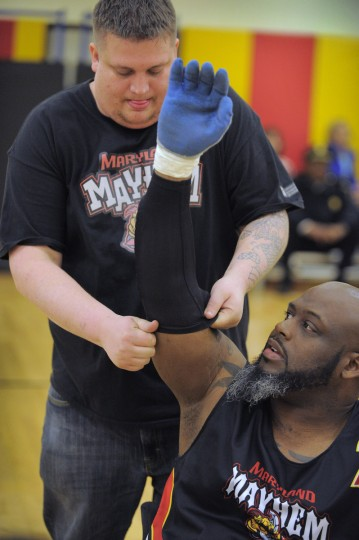 Maryland Mayhem assistant coach Billy Hardester helps player Louis Fortune prepare to compete during the first Crab Pot Tournament. (Karl Merton Ferron/Baltimore Sun)