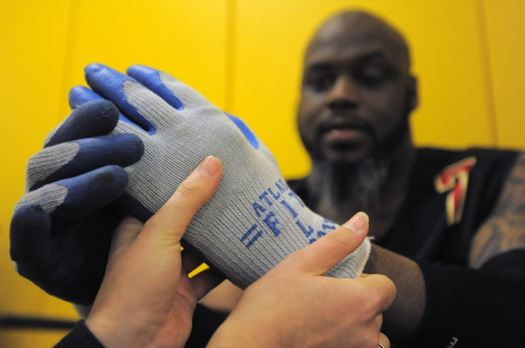 Occupational therapy student Laura Karp helps place utility gloves on Maryland Mayhem player Louis Fortune during the first Crab Pot Tournament at University of Maryland Rehabilitation & Orthopaedic Institute. (Karl Merton Ferron/Baltimore Sun)