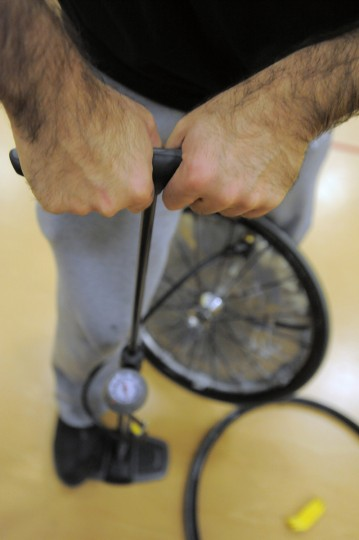 Volunteer Chris Clark pumps air into a rugby chair wheel during the Crab Pot Tournament at University of Maryland Rehabilitation & Orthopaedic Institute. (Karl Merton Ferron/Baltimore Sun)