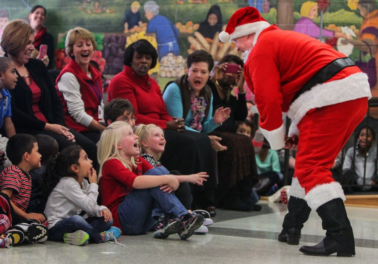 Josh Risher surprises his daughters, Christy Risher, 8, and Kaylee Risher, 6, by masquerading as Santa Claus in a school musical on Dec. 10, 2014 at Windsor Elementary School in Columbia, S.C. Risher had been deployed with the army for a year in South Korea. (Tracy Glantz/The State/TNS)