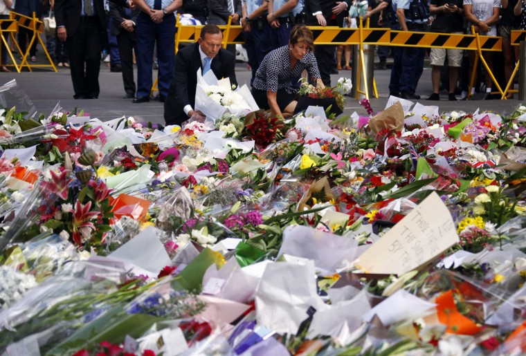 Australian Prime Minister Tony Abbott and his wife Margie place floral tributes amongst thousands of others near the Lindt cafe, where hostages were held for over 16-hours, in central Sydney December 16, 2014. Heavily armed Australian police stormed the Sydney cafe early on Tuesday morning and freed a number of hostages being held there at gunpoint, in a dramatic end to a 16-hour siege in which three people including the attacker were killed. (REUTERS/David Gray)