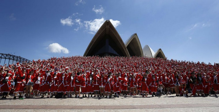 Thousands of runners in Father Christmas suits pose for a group photo after completing an annual Santa fun run from Darling Harbor to the Sydney Opera House, December 7, 2014. The annual event is held each year as a fundraiser to assist disadvantaged children with equipment and programs to help them live a fuller life. (Jason Reed/Reuters)