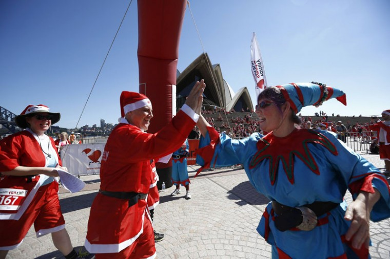 A Santa 'elf' congratulates a runner across the finish line after completing the annual Santa fun run from Darling Harbor to the Sydney Opera House, December 7, 2014. The annual event is held each year as a fundraiser to assist disadvantaged children with equipment and programs to help them live a fuller life. (Jason Reed/Reuters)