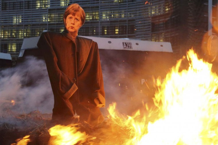 An effigy of German Chancellor Angela Merkel is seen near burning bales of straw set on fire by European farmers during a protest against the Transatlantic Trade and Investment Partnership (TTIP) near the European Commission headquarters in Brussels December 19.  || PHOTO CREDIT: PASCAL ROSSIGNOL  - REUTERS