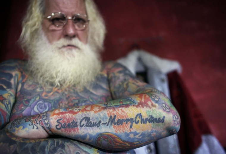Vitor Martins displays one of his Christmas tattoos inside his house, before a performance with children in Sao Caetano do Sul's town square, near Sao Paulo, December 7, 2014. Martins has dressed as Santa Claus, working at shopping centers and various events, for fifteen years, and has 94 percent of his body covered in tattoos, with several in reference to Christmas. (Nacho Doce/Reuters)