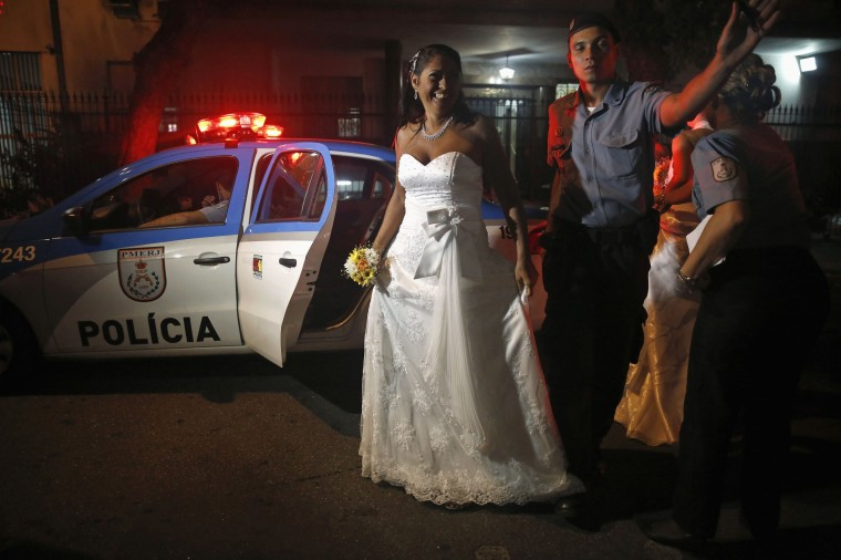A bride from the Santa Marta slum is escorted by a police officer to her group wedding in Rio de Janeiro December 17, 2014. A total of 16 couples took part in a mass wedding ceremony organized by the Police Peacekeeping Unit (UPP) as part of activities geared towards social enhancement of the slums. REUTERS/Pilar Olivares