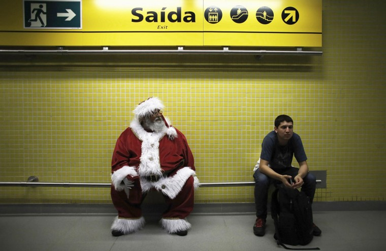 A man, dressed as Santa Claus, waits to board a train at a subway station as part of a promotional event by a bank in Sao Paulo. (Nacho Doce/Reuters)