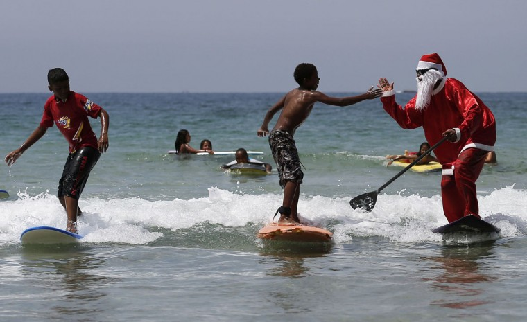 Carlos Bahia, dressed as Santa Claus, jokes with a child as they surf at the Maresias beach, in the state of Sao Paulo December 9, 2014. In the Southern Hemisphere summer starts on December 1, so while countries in the north are experiencing a white Christmas with grey skies, those in the south are busy surfing and sunbathing in temperatures just shy of 100 degrees Fahrenheit (38 degrees Celsius). Picture taken December 9, 2014. (Nacho Doce/Reuters)