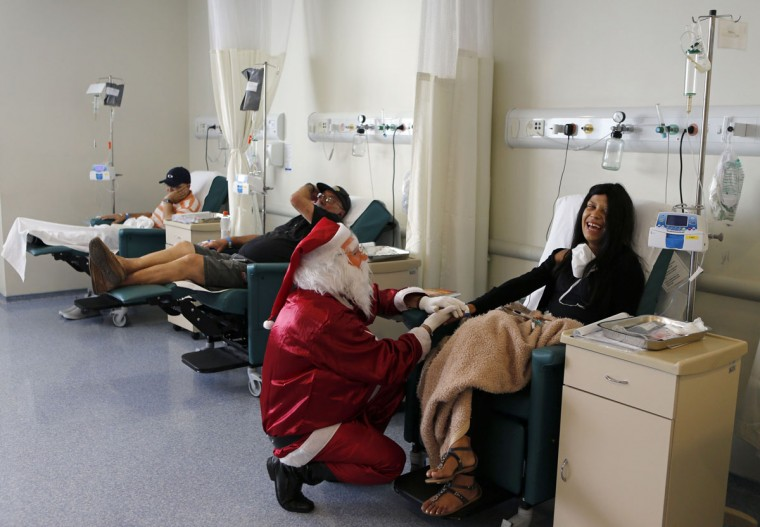 A man dressed as Santa Claus talks to a cancer patient undergoing chemotherapy in the Cancer Institute in Sao Paulo December 19, 2014. (Paulo Whitaker/Reuters)