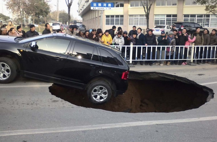People look at a car hanging on the edge of a caved-in area on a street in Zhenjiang, Jiangsu province December 12. The street collapsed on Friday morning as the car drove by and formed the pit measuring 2m (6.7ft) in depth and 5m (16.4ft) in diametre, according to local media.    || PHOTO CREDIT: STRINGER  - REUTERS